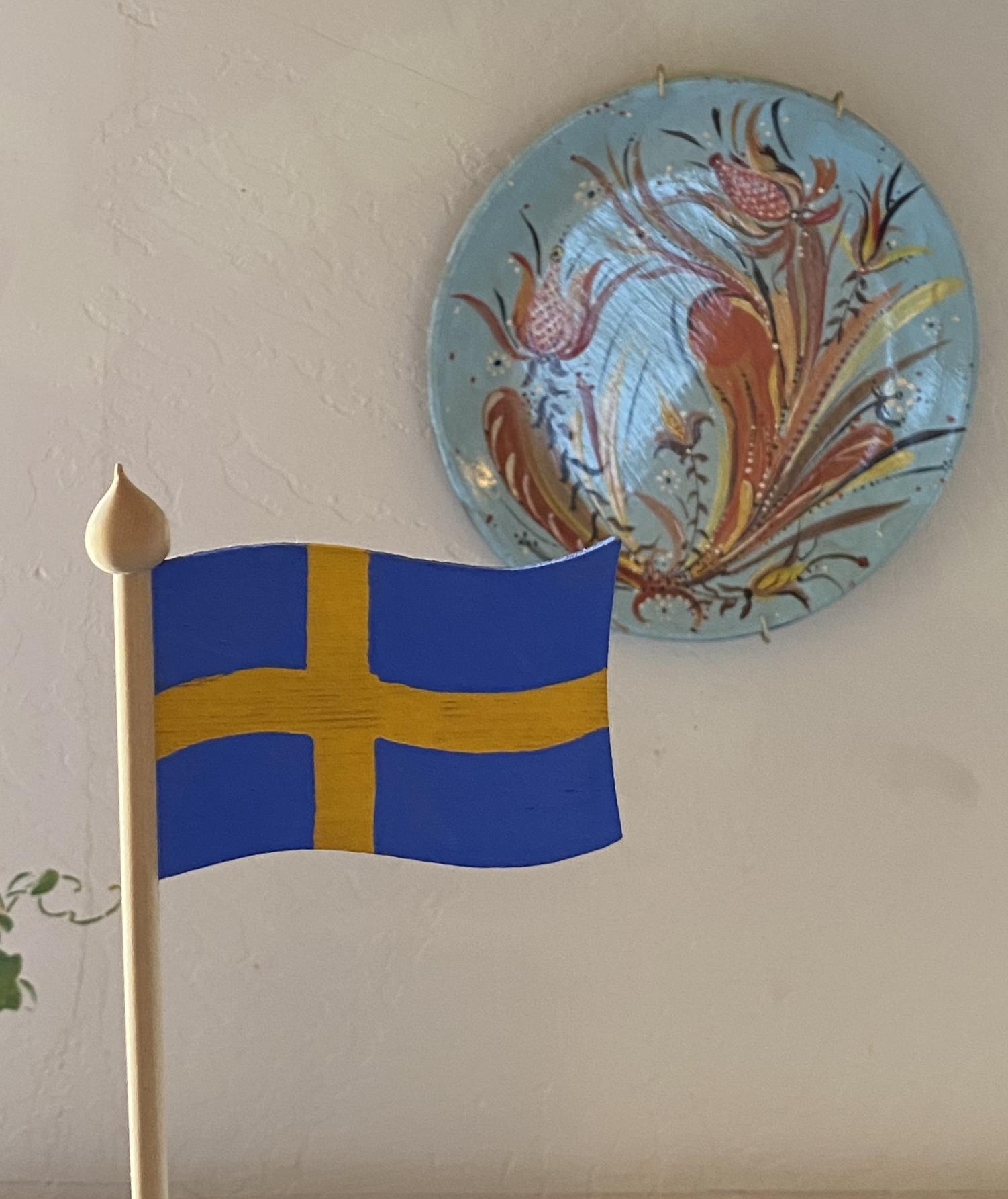 A Swedish flag in Grandmas Swedish Bakery, with Swedish folk art in the background